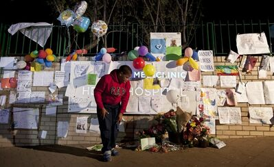 """Yongama, 9, observes bunches of flowers after leaving a get-well card at the entrance to the Mediclinic Heart Hospital where former South African President Nelson Mandela is being treated in Pretoria, South Africa Monday, June 24, 2013. South Africa's president Jacob Zuma on Monday said a critically ill Nelson Mandela was """"asleep"""" when he visited the 94-year-old in a hospital, and he urged the country to pray for Mandela, describing him as the """"father of democracy"""" who made extraordinary sacrifices on behalf of his people. (AP Photo/Ben Curtis)"""