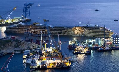 "The Costa Concordia is seen after it was lifted upright, on the Tuscan Island of Giglio, Italy, early Tuesday morning, Sept. 17, 2013. The crippled cruise ship was pulled completely upright early Tuesday after a complicated, 19-hour operation to wrench it from its side where it capsized last year off Tuscany, with officials declaring it a ""perfect"" end to a daring and unprecedented engineering feat. (AP Photo/Andrew Medichini)"