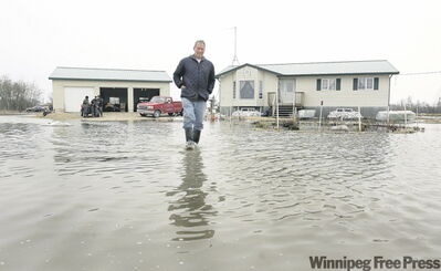 St. Clements resident Roger Trueman walks down what used to be his driveway after being up all night pumping water out of his home.