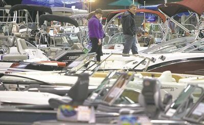 Photos by TREVOR HAGAN / WINNIPEG FREE PRESSABOVE: A couple browses the shiny new boats during the 2013 Mid-Canada Boat Show at the Winnipeg Convention Centre on Friday. ABOVE RIGHT: Noah Chartrand gets behind the wheel as he and his brother, Banx check out the 22-foot fish and ski pontoon boat their parents just bought.