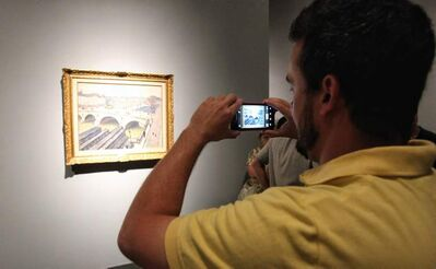 Chris Otis snaps a photo of an Albert Marquet painting on the final day of the 100 Masters: Only in Canada exhibition at the Winnipeg Art Gallery Monday.