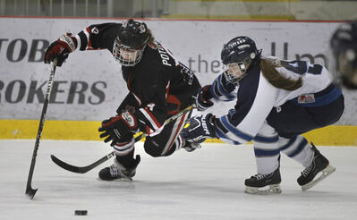 At right, Shaftesbury Titans defenceman Cydnee Cook is penalized for a takedown of Sarah Potomak forward on the Pursuit of Excellence team from Kelowna, B.C.  at the Female Sport School Challenge at the MTS Iceplex Friday morning.