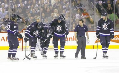TREVOR HAGAN / WINNIPEG FREE PRESSA whole passel of Jets are on hand to help as Blake Wheeler (third-left) limps off the ice after blocking a shot in the second period.