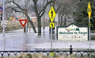 Fargo on April 8, 2011. A 98 per cent chance of major Fargo flooding is predicted this year.  The Fargo, N.D., welcome sign sits in floodwaters while Kent Heckendoft, background, left, assistant flood engineer for the U.S. Army Corps of Engineers, inspects the levee protecting the downtown from the rising floodwaters of the Red River, Friday, April 8, 2011.  (AP Photo/Jim Mone)