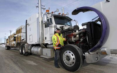 Trucker Kelly Ring checks his rig in Winnipeg last week before hauling building supplies to Garden Hill First Nation. It's a 1,000-kilometre round trip over treacherous ice roads.