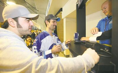 TREVOR HAGAN / WINNIPEG FREE PRESSEveryone wants to rub Carlos Labao, middle, for luck after he won two 50-50 draws at the MTS Centre totalling more than $80,000. His friend, Gio DiNoto, left, hoped the two could share in the spoils at Saturday�s Winnipeg Jets game if Labao was lucky for the third time.