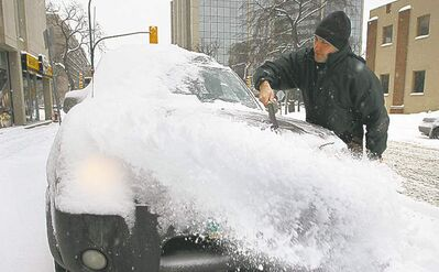 Andrej Kazancev clears snow from his truck Monday morning.