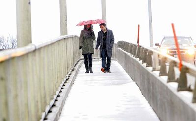 Suzanne Carpanini and Francisco Portillo walk on the pedestrian portion of the St. James Bridge amid Saturday's snowfall. A city plan aims to make walking a more attractive option.