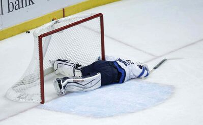 Jets goalie Al Montoya lies on the ice after a collision with Blackhawks forward Marian Hossa.