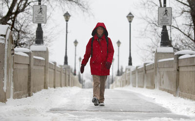 Tamara Dyck makes her way over the Assiniboine Park footbridge on her way to work Saturday morning in the fresh fallen snow.
