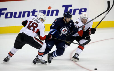 Ottawa Senators' Jim O'Brien, Winnipeg Jets' Andrew Ladd and Sens' Troy Rutkowski (right) battle for the puck during play at the MTS Centre on Sunday.