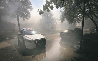 A smoke haze fills the air on Nichol Avenue Friday afternoon as two homes were destroyed by fire.