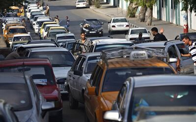 Palestinians wait in queue to refuel their cars at a gas station in Gaza City, Monday, Sept. 2, 2013. Egyptian military's caving in smuggling tunnels along the Egyptian border with the Gaza Strip Sunday caused a fuel shortage at some of the gas stations in the Gaza Strip. (AP Photo/Adel Hana)