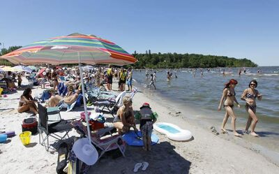 A few thousand people enjoy the sunshine at Grand Beach on Canada Day in 2012. Sunbathers won't be able to smoke on beaches starting in 2014, provincial officials announced Thursday.