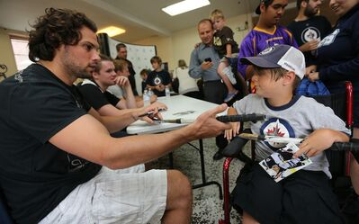 Winnipeg Jets defenceman Zach Bogosian signs an autograph for Luke Armbruster, 9, at the Rehabilitation Centre for Children Wednesday.