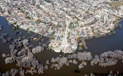 MICHAEL VOSBURG / THE FORUMThe flooding Red River laps against houses Tuesday on Woodcrest Drive in Fargo, N.D. Interstate 29 has been closed north of the city because of flooding.