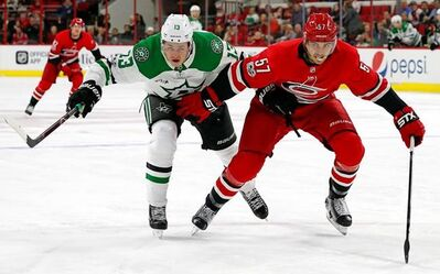 Dallas Stars' Esa Lindell (23) and Carolina Hurricanes' Trevor van Riemsdyk (57) eye the puck during the first period of an NHL hockey game, Monday, Nov. 13, 2017, in Raleigh, N.C. (AP Photo/Karl B DeBlaker)