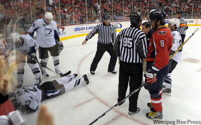 Alexander Ovechkin slams Jamie Heward into the boards and Heward crumples to the ice (opposite page). Ovechkin looks on (left) as Heward is attended to and carried off the ice.