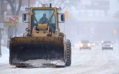 A loader drives along snow-covered Pembina Highway near Fleet Street, Monday. Expect to see many of these on the streets today.