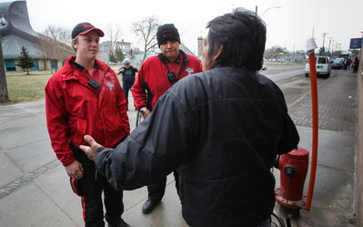 Downtown BIZ Watch volunteer Tanner Magalas (left) and Robert Catagas chat with a homeless man outside the Salvation Army building on Main Street.