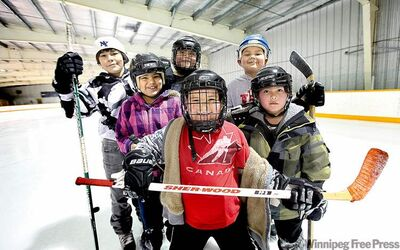 Kids take a break from shooting pucks to pose for a photo in the Ebb and Flow arena after school.  (L-R): Matthew McIvor, Joclynn Houle, Layne Houle, Chase Houle,  Rueben Houle, and Leland Malcoln. The reserve was once dubbed one of the worst in the province. That reputation is quickly changing.