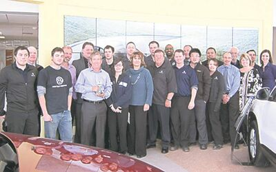 Auto Haus Volkswagen sales reps and service technicians. General manager Gerald Boiteau is holding Wolfsburg trophy.