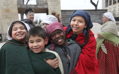 Students play together dressed in 1860's period costume as they attend the unveiling of the Upper Fort Garry Provincial Park Saturday. Oct 17,  2014