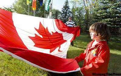 Melody McCurdy, 4, helps her uncle Shayne Campbell (rear) open one of the Canadian flags housed at the Argyle Prairie Museum.