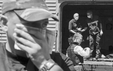 A man covers his face with a rag Monday due to the odour as deputy head of the OSCE mission to Ukraine, Alexander Hug (bottom right), and members of the Netherlands' National Forensic Investigations Team inspects bodies from the crash of Malaysia Airlines Flight 17 in a refrigerated train in eastern Ukraine.