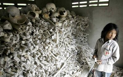 Cambodian Meo Soknen, 13, stands inside a small shrine full of human bones and skulls, all victims of the Khmer Rouge.  The small shrine, located 27 kilometers, south of Phnom Penh is one of many out of the way and forgotten monuments to the 'Killing Fields.'