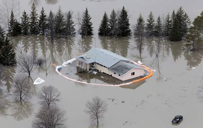 A house with a breached sandbag dike is flooded off Breezy Point Road north of Selkirk during the 2011 flood. A task force says the 2011 flood was the largest and most severe in the province's recorded history.