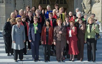 Women MPs from all four parties gathered in front of the Centre Block on Parliament Hill, March 8, 2010, for a group photo in support of CARE Canada and International Women's Day.  The string on their fingers is a CARE initiative to remember to stand in solidarity with women and girls around the world.