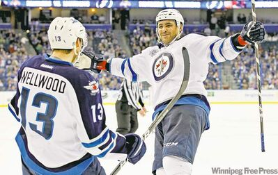 Mike Carlson / the associated pressOvertime hero Kyle Wellwood celebrates his game-winning goal with newly returned teammate Dustin Byfuglien.