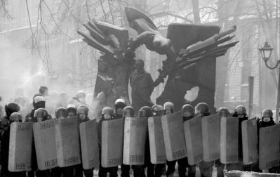 Riot police block a street in front of protesters in Kyiv, Ukraine on Friday.