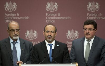 FILE - In this Oct. 22, 2013, file photo, Syrian National Coalition chief Ahmed Jarba, center, Heitham Al-Maleh, left, and Salem Al-Muslit speak to the media at the British Foreign Office in London. Two weeks ahead of an international peace conference on Syria, the country's main Western-backed opposition group stands on the brink of collapse, dragged down by outside pressures, infighting and deep disagreements over the basic question of whether to talk to President Bashar Assad. (AP Photo/Alastair Grant, File)