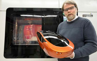 Inventor and designer Jim Kor of Winnipeg, Manitoba, shows off a 1/6th-scale model of Urbee 1, a full-sized thermoplastic eco-friendly electric-ethanol car 'printed' with 3D technology at the RedEye facility in Eden Prairie, Minn.