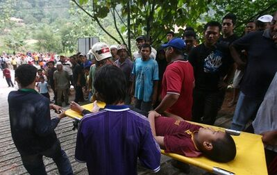 People carry an orphan injured in a landslide in Hulu Langat in central Selangor state, outside Kuala Lumpur, Malaysia, Saturday, May 21, 2011. Police say about 30 children were buried by the landslide that hit an orphanage Saturday. (AP Photo) MALAYSIA OUT
