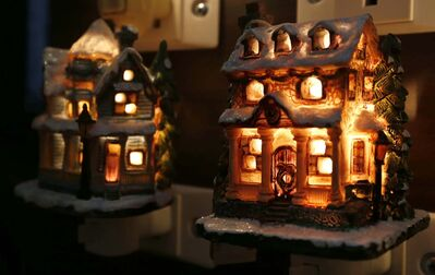 Decorative Christmas-themed houses bringing a festive glow to a room.</p>