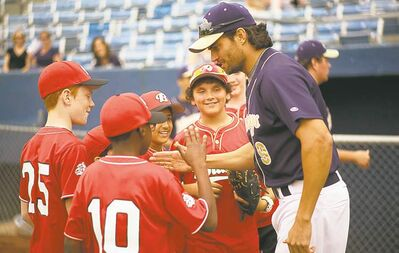 Scott Elrod (right) talks to young fans in Home Run. 