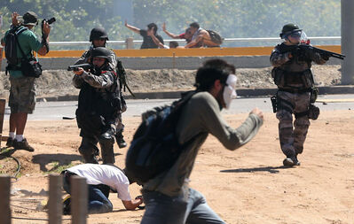 Riot police aim their weapons at protesters gathering near Castelao stadium in Fortaleza, Brazil.