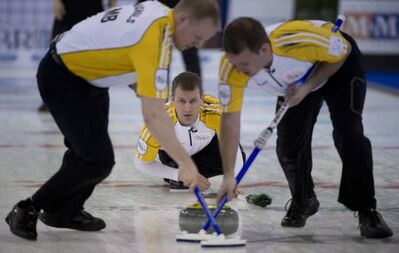 Manitoba skip Jeff Stoughton calls a shot as lead Mark Nichols (left) and second Reid Carruthers sweep during the evening draw against Ontario at the Tim Hortons Brier in Edmonton on Sunday.