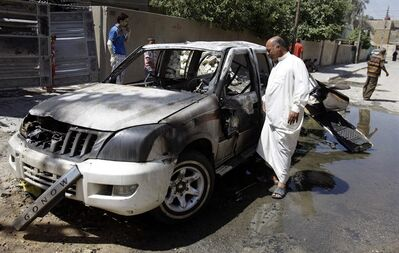 Civilians inspect the aftermath of a car bomb attack in Baghdad, Iraq, Wednesday, July 24, 2013. A bomb exploded near a Sunni mosque in Baghdad's southern Dora neighborhood on Tuesday killing several people and wounding many, police said. (AP Photo/Karim Kadim)