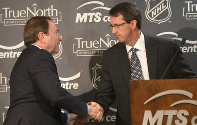 Mark Chipman of True North Sports and Entertainment LTD , right, is congratulated by NHL commissioner Gary Bettman after the announcement of the NHL return to Winnipeg yesterday.