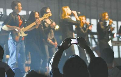 A Kodiak, Alaska Coast Guardsman holds up his iPhone for a picture of the USO concert featuring the Gary Sinise and the Lt. Dan Band Monday night, June 25, 2012 in Kodiak Coast Guard Hangar 3. (AP Photo/James Brooks, Kodiak Daily Mirror)