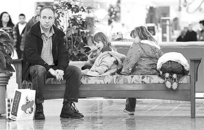 FILE - In this Friday, Dec. 23, 2011 file photo, Mike Hettmann of Green Bay and his daughters Allison, 5, Audrey, 6, and Samantha, 4, right, wait patiently for their mother to finish last minute Christmas shopping at the Fox River Mall in Grand Chute, Wis. (AP Photo/The Post-Crescent, Dan Powers, File) NO SALES