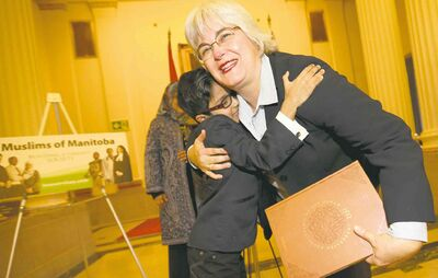 Kaleem gets a hug from Manitoba Immigration and Multiculturalism Minister Christine Melnick for giving her a Qur'an reference book after she proclaimed October Islamic History Month.