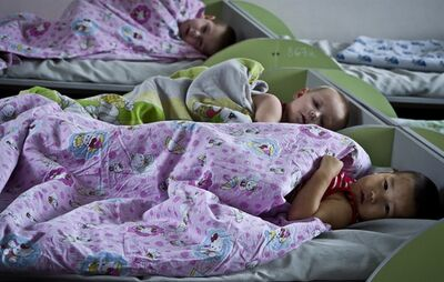 Kyrgyz orphans are in bed in an orphanage in Bishkek, Kyrgyzstan, Thursday, Jan. 31, 2013. Americans were in process of adopting 65 orphans from Kyrgyzstan when it suspended international adoptions in 2008 due to allegations of fraud. Some of the Americans gave up, some of the children were placed in domestic adoptions, and last summer nine of the remaining children finally were allowed to go to America. There are now 16 U.S. families still waiting, five year later. (AP Photo/Abylay Saralayev)