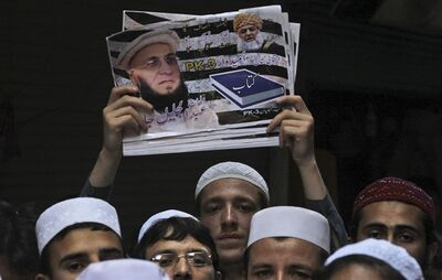 In this Tuesday, April 16, 2013 photo, a supporter of Maulana Jalil Jan, a candidate of Jamiat Ulema-e-Islam, holds up a poster of Jan, during a tour by Jan in a market in Peshawar, Pakistan. Moderate politicians from some of Pakistan's most violent areas are defying the threat of violence to run in upcoming nationwide elections, but they're increasingly turning to social media and phone calls that allow them to campaign from a distance. (AP Photo/Mohammad Sajjad)