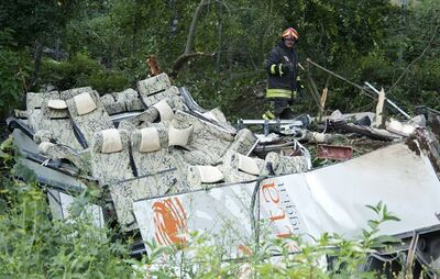 A firefighter looks at the wreckage of a bus which crashed off a highway near Avellino, southern Italy, Monday, July 29, 2013. Rescuers wielding electric saws cut through the twisted wreckage of an Italian tour bus for survivors of a crash in southern Italy that killed at least 37 people after it crashed into traffic and plunged into a ravine on Sunday night. Reports said as many as 49 people, mostly Italians, had been aboard the bus when it ripped through a guardrail, then plunged some 30 meters (100 feet) off a viaduct near a wooded area. (AP Photo/Salvatore Laporta)
