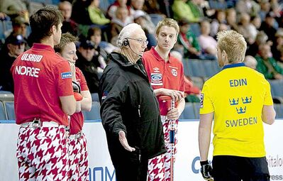 An official speaks with Niklas Edin (right) and Norway skip Thomas Ulsrud.